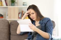 Lesende schlechte Nachrichten der beteiligten Frau in einem Buchstaben stockfotografie