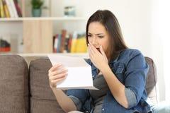 Lesende schlechte Nachrichten der traurigen Frau in einem Papierbuchstaben stockfotografie