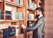 Leser steht nahen Bücherschrank und wählt Buch lizenzfreies stockfoto