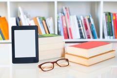 Leser und Lesebrille Ebook auf Bücherregalhintergrund Kopieren Sie Raum auf digitaler Tablettenanzeige lizenzfreie stockfotografie