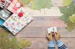 Lesewidmung von Geschenken auf Holztisch mit Herbstlaub Lizenzfreie Stockfotos
