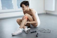 Lesión de pierna Dolor hermoso de la sensación de la mujer en la rodilla, rodilla dolorosa imágenes de archivo libres de regalías