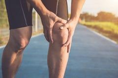 Lesione dal concetto di allenamento: Le mani asiatiche di uso dell'uomo tengono sul suo kn Fotografia Stock