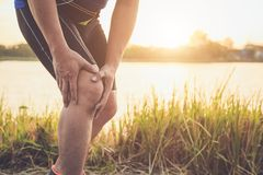 Lesione dal concetto di allenamento: Le mani asiatiche di uso dell'uomo tengono sul suo kn Immagine Stock