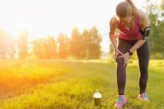 Lesiones - deportes que corren la lesión de rodilla en mujer Imágenes de archivo libres de regalías