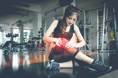 Lesioni asiatiche della donna durante l'allenamento al ginocchio nella palestra di forma fisica Medi fotografie stock libere da diritti