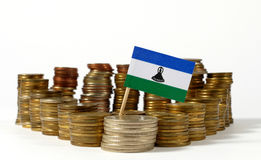 Lesotho flag with stack of money coins. Lesotho flag waving with stack of money coins stock photo
