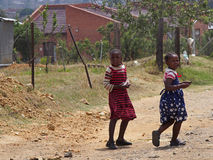 LESOTHO GIRLS. Two young girls in pretty dresses make their way along a dusty road in Maseru, Lesotho Stock Photos