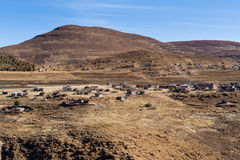 Lesotho Village. A village in rural Thaba-Tseka District with a mixture of modern and traditional houses soaks in the sun on a dry winter afternoon in the royalty free stock image