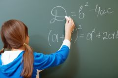 At lesson. Confident student pointing at formula on blackboard during algebra lesson Royalty Free Stock Images