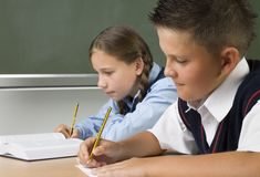 At the lesson. Young girl and boy sitting at desk and writing something. Boy is smiling. Side view Stock Image