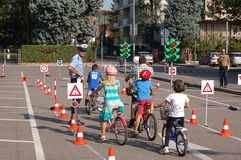 Lesson. The childrens with their bicycle are learning, with a police officer, what to do when the traffic ligh is red so they must stop and when the traffic royalty free stock images