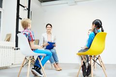 Lesson in circle. School seminar in classroom without desks where kids and teacher sitting on chairs in circle and having discussion Royalty Free Stock Photography