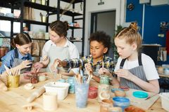 Lesson of creativity. Group of creative kids and their teacher painting handmade clay items at lesson of handcraft Royalty Free Stock Photography
