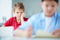 Lesson is dull. Portrait of bored schoolboy looking at camera while drawing at lesson stock photo