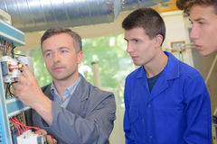 Lesson with electrician and two apprentices Royalty Free Stock Photo