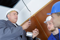 Lesson with electrician and two apprentices Stock Photo
