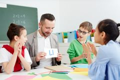 Lesson of English. Confident middle aged English teacher of secondary school showing his pupils cards with letters at lesson Stock Photos