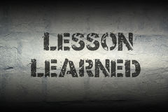 Lesson learned gr. Lesson learned stencil print on the grunge white brick wall; specially designed font is used Royalty Free Stock Image