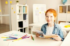 Lesson of literature. Youthful learner with open book siting by desk at lesson of literature Stock Images