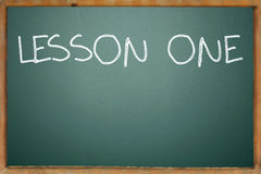 Lesson one. Text on the green blackboard Royalty Free Stock Image