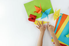 Lesson of origami. Children`s hands do origami from colored paper on white background. lesson of origami stock photo