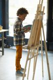 Lesson of painting. Clever schoolboy in casualwear standing in front of easel and painting picture at lesson Royalty Free Stock Photo