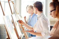 During lesson of painting. Creative guy looking at picture on easel of teacher while painting at lesson in studio of arts Royalty Free Stock Photo