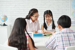 Lesson. Teacher explaining something to students in classroom stock photos