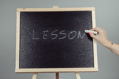 Lesson written in white chalk on a black chalkboard Royalty Free Stock Image