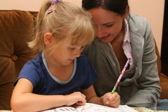 Lesson14. Young girl is learning from her first book with her mother Royalty Free Stock Photography