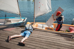 Lessons in Kaunas sailing school for children. Kaunas, Lithuania - June 10, 2014: Lessons in Kaunas sailing school for children. Two children launching small Stock Photography