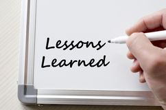 Lessons learned written on whiteboard. Human hand writing lessons learned on whiteboard Stock Photos