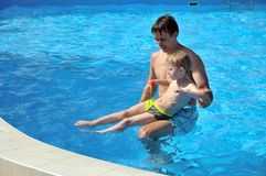 Lessons of swimming. Father teaching his little son to swim, they are smiling, they are happy Royalty Free Stock Photography