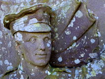 Face of soldier on lichen covered memorial Stock Photography