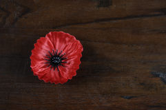 Lest We Forget, Red Poppy Lapel Pin Badge on dark recycled wood with copy space. Stock Photos