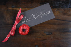 Lest We Forget, Red Poppy Lapel Pin Badge on dark recycled wood Stock Image