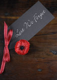 Lest We Forget, Red Poppy Lapel Pin Badge on dark recycled wood - vertical Stock Photo