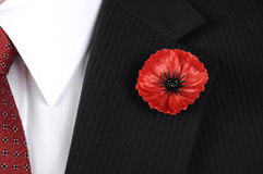 Lest We Forget Red Poppy Lapel Pin Badge on man's black suit. Royalty Free Stock Images
