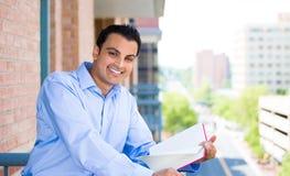 Lesung des gutaussehenden Mannes auf Balkon lizenzfreie stockbilder