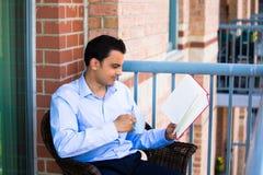 Lesung des gutaussehenden Mannes auf Balkon stockbild