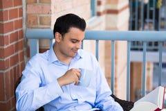 Lesung des gutaussehenden Mannes auf Balkon stockfotos