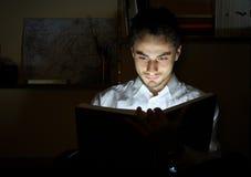 Lesung des jungen Mannes in einer Bibliothek Stockbild