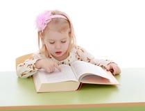 Lesung des kleinen Mädchens an einem Tisch Stockfotos