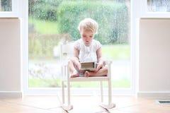 Lesung des kleinen Mädchens vor großem Fenster Lizenzfreie Stockfotos