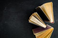 Lesung und selbstständige Entwicklung Alte Bücher auf schwarzem Draufsicht-Kopienraum des Hintergrundes Stockfotografie
