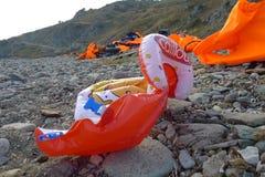 LESVOS,希腊2015年10月24日:救生衣,橡胶dinghys片断在海滩放弃在Molyvos附近的橡胶环 免版税库存照片