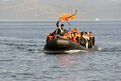 LESVOS, ГРЕЦИЯ 12-ое октября 2015: Беженцы приезжая в Грецию в тусклой шлюпке от Турции Стоковые Изображения