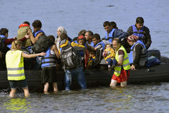 LESVOS, ГРЕЦИЯ 12-ое октября 2015: Беженцы приезжая в Грецию в тусклой шлюпке от Турции стоковое фото