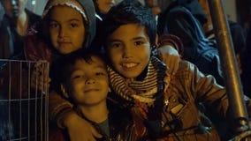 LESVOS, GRÉCIA - 5 DE NOVEMBRO DE 2015: As crianças do refugiado sorriem à câmera na noite na noite filme